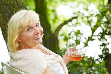 Alte Frau beim Tee trinken im Garten