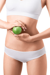 Slim woman in white underwear with green apple at her hands over