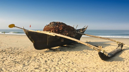 Old boat with fishing net on a sandy beach. India. Goa