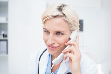 Doctor using telephone while looking away