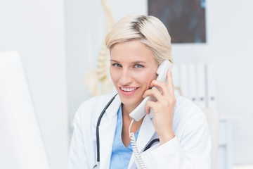 Female doctor using land line phone in clinic