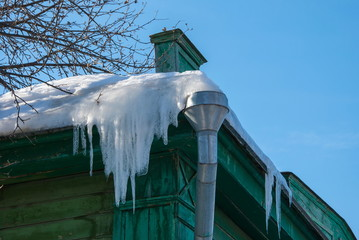Icicles on the roof of an old wooden house