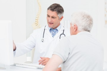 Doctor explaining reports to senior patient on computer