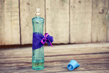 Blue perfume bottle on the wooden background. Toned image.