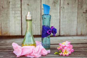 Blue and green perfume bottles near flowers fresia.