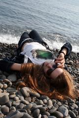 Рыжая девушка лежит на гальке, на берегу