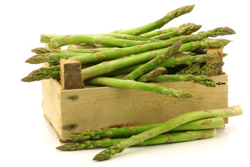 fresh green asparagus shoots in a wooden crate on a white backg