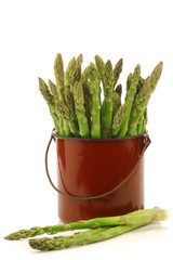 fresh green asparagus shoots in a brown enamel cooking pot