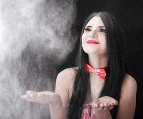 Portrait of a woman catching a white powder