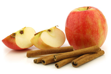 dried cinnamon sticks,  fresh apples on a white background