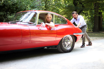 Mann schiebt roten Roadster