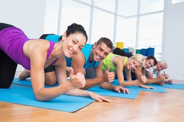 People gesturing thumbs up while lying on exercise mats