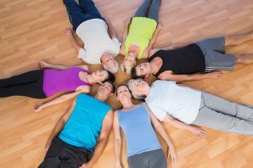 People lying in circle on hardwood floor at gym