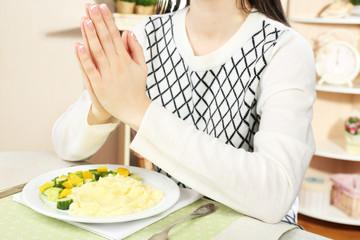 Woman praying before eating