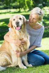 Happy blonde hugging her dog in the park