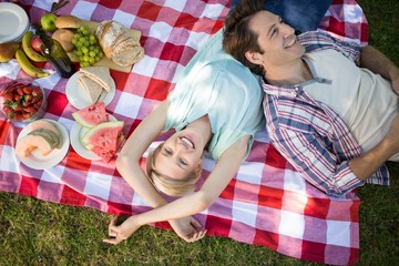 Happy couple lying together at the park