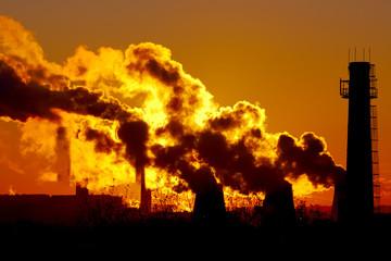 power plant smokestacks at sunset