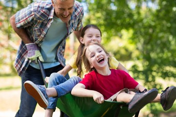 Happy father and his children playing with a wheelbarrow