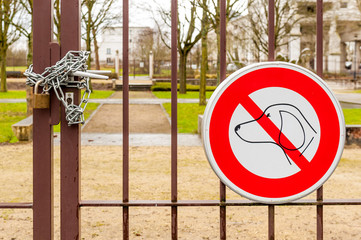 No dogs allowed sign and locked park gate