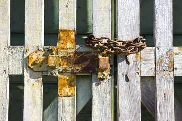 Old wooden gate closed with padlock