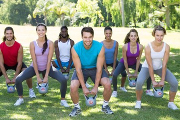 Fitness group squatting in park with kettle bells