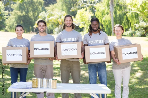 Happy volunteers with donation boxes in park - 78780132