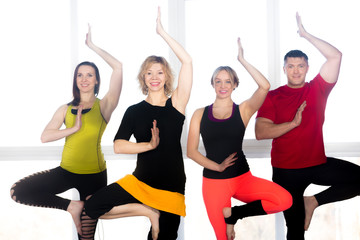 Group of four positive people doing Yoga practice in class