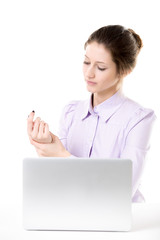 Young woman rubbing her hand after working on laptop
