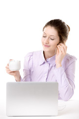 Young woman enjoying music with cup of coffee in front of comput