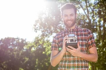 Handsome hipster holding vintage camera