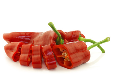 fresh whole and cut red sweet peppers on a white background