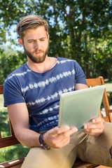 Young man using tablet on park bench