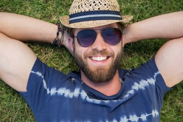 Handsome hipster lying on grass