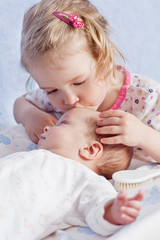 Cute Toddler sister kisses newborn