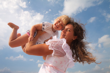 family, child and happiness concept - mother throws up her