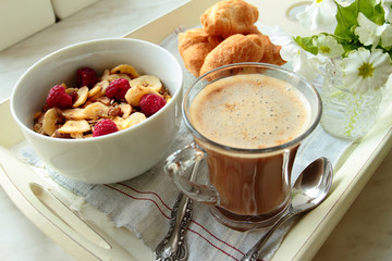 Tray with coffee, cereals, croissants for breakfast