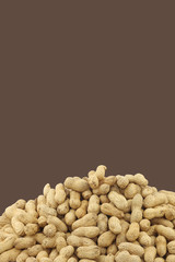bunch of roasted peanuts on a brown background