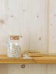 A jar of oatmeal flakes and wheat on a wooden shelf