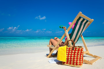 Young girl lying on a beach lounger with glasses in hand on the