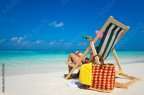 Papiers peints Detente Young girl lying on a beach lounger with glasses in hand on the