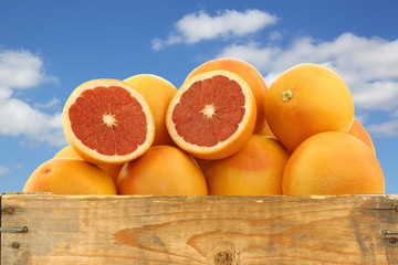 fresh red grapefruits and a cut one in a wooden crate