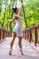 Girl dancer stands on tiptoes, ballet pirouette. Outdoors