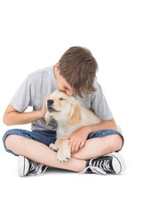 Boy kissing puppy over white background