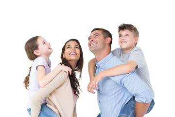 Parents giving piggyback ride to children while looking up