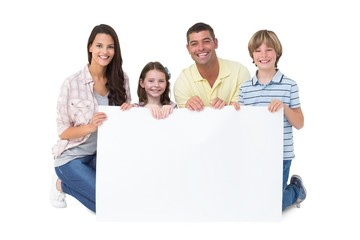Happy family holding billboard over white background