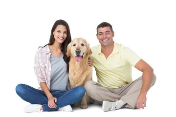 Happy couple with dog sitting over white background