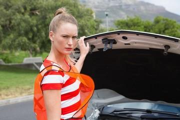 Worried young woman beside her broken down car