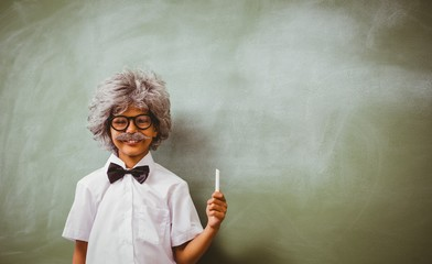 Boy dressed as senior teacher in front of blackboard