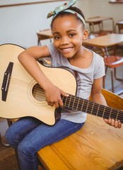 Little girl playing guitar in classroom