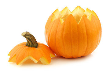 An orange Halloween pumpkin cut open on a white background